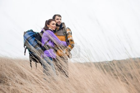 Young backpackers standing in dry grass