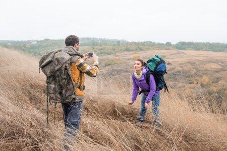 Photo pour Jeune homme photographiant belle femme brune lors d'une promenade à la campagne - image libre de droit