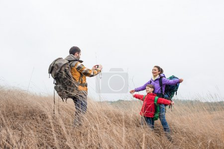 Man photographing wife and son with backpacks
