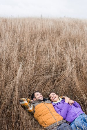 Happy young couple lying in grass