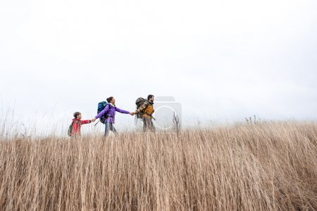 Photo for Low angle view of happy family with backpacks holding hands and walking in tall grass against cloudy sky - Royalty Free Image