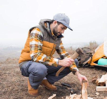 Photo pour Jeune homme barbu coupant du bois de chauffage avec hache près de la tente - image libre de droit