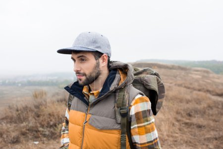 Photo pour Gros plan portrait de jeune homme barbu avec sac à dos debout et regardant loin dans la campagne - image libre de droit