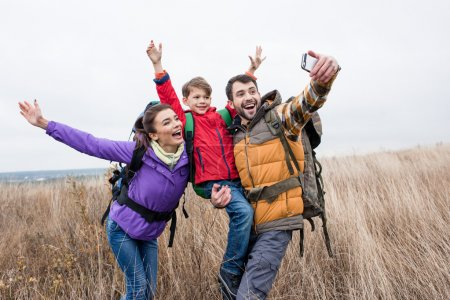 Photo for Happy family with backpacks standing in tall grass and taking selfie at autumn day - Royalty Free Image