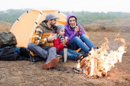 Photo pour Famille avec un enfant assis près de la tente et boire du thé chaud du thermos tout en se reposant près du feu brûlant dans la campagne - image libre de droit
