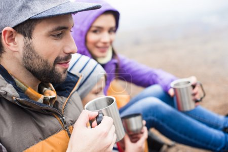 Photo for Side view of smiling family drinking hot tea from metal cups while sitting outdoors - Royalty Free Image