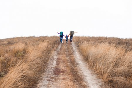 Photo for Back view of happy young family with backpacks holding hands and running on rural path at cloudy autumn day - Royalty Free Image