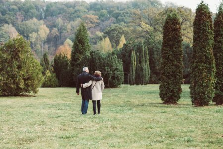 Mature couple walking in autumn park