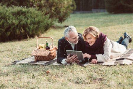 Photo pour Beau couple d'âge mûr souriant utilisant une tablette numérique tout en étant couché sur plaid avec panier de pique-nique dans le parc d'automne - image libre de droit