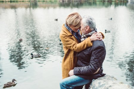 Happy mature couple hugging near lake