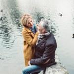 Happy mature couple hugging near lake