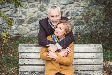 Photo pour Beautiful smiling mature couple hugging on wooden bench outdoors - image libre de droit