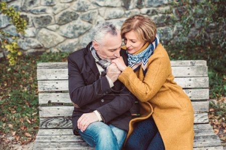Photo for Beautiful mature couple sitting on wooden bench - Royalty Free Image