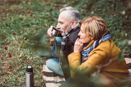 Mature couple drinking tea in park