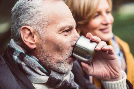 Photo pour Gros plan portrait de beau couple mature buvant du thé chaud du thermos dans le parc d'automne - image libre de droit