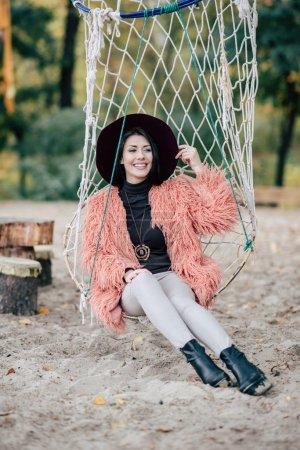 Attractive woman sitting in net swing