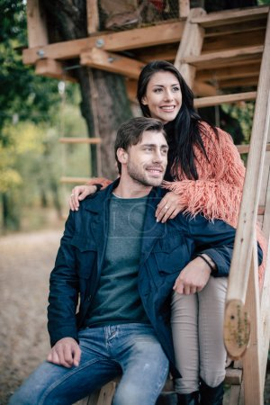 Photo for Portrait of happy young loving couple posing on stairs of tree house - Royalty Free Image