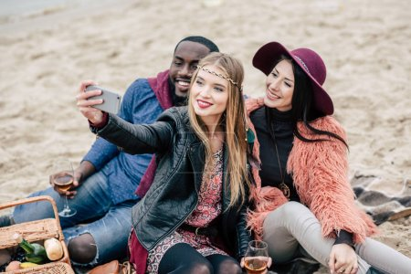 Happy people taking selfie at picnic