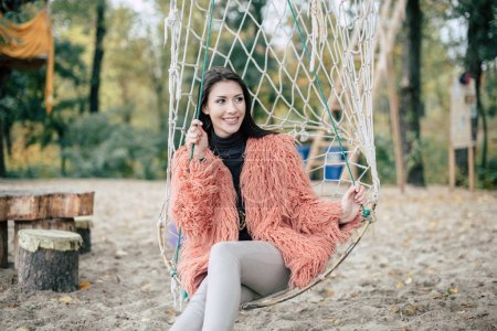 Photo for Attractive fashionable young woman sitting in net swing on sandy beach - Royalty Free Image