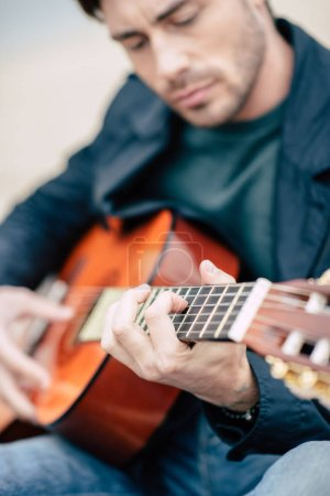 Photo for Close-up view of handsome young man playing guitar outdoors - Royalty Free Image