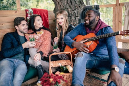 Photo for Four smiling young friends holding glasses with cocktails and enjoying guitar at picnic - Royalty Free Image