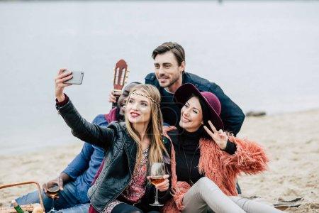 Photo pour Jeunes gens heureux prenant selfie tout en étant assis sur la plage de sable fin à pique-nique en plein air - image libre de droit