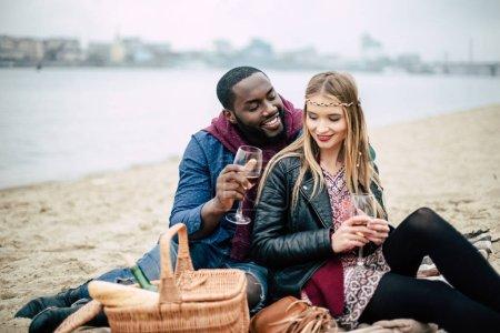 Photo pour Beau jeune couple romantique assis sur une plage de sable avec des verres de vin et un panier au pique-nique en plein air - image libre de droit