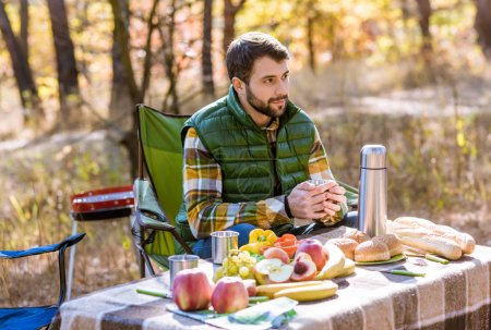 Smiling man sitting at table on picnic