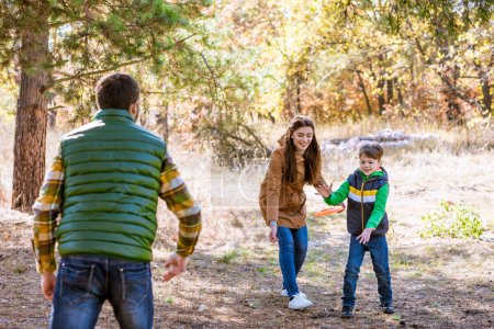 Photo for Happy family playing with frisbee and having fun in autumn park - Royalty Free Image