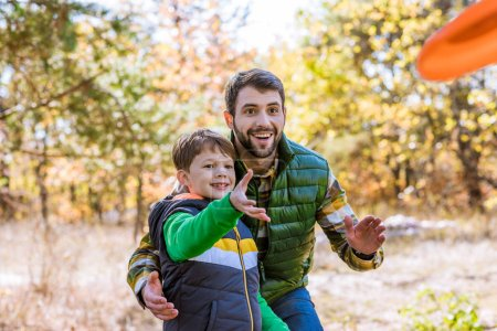 Photo for Smiling father and cute little son playing with frisbee and having fun in autumn park - Royalty Free Image