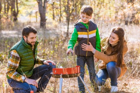 Happy family preparing barbecue in park