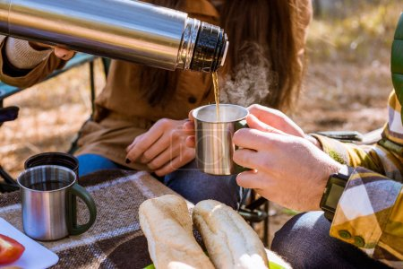 Photo for Close-up view of  pouring hot tea from thermos into cup - Royalty Free Image