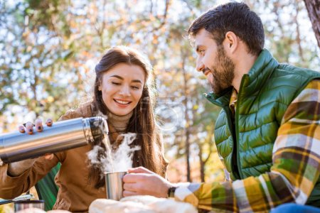 Photo for Close-up portrait of smiling young woman pouring hot tea from thermos to young bearded man sitting outdoors at sunny autumn day - Royalty Free Image