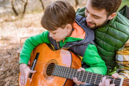 Father teaching son playing guitar