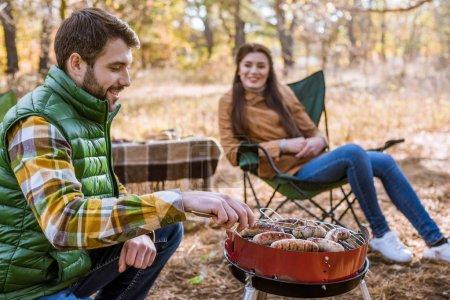 Smiling man grilling sausages