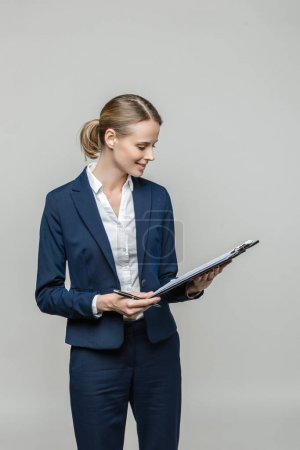 Photo for Smiling businesswoman with clipboard and documents, isolated on grey - Royalty Free Image