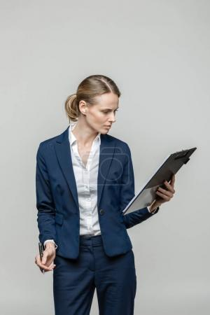 Photo for Serious businesswoman with clipboard and documents, isolated on grey - Royalty Free Image
