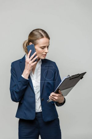 businesswoman with paperwork and smartphone