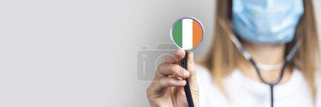 Photo pour Femme médecin dans un masque médical tient un stéthoscope sur un fond clair. Ajouté le drapeau de la Côte d'Ivoire. Concept médecine, niveau de médecine, virus, épidémie. Baner ! . - image libre de droit