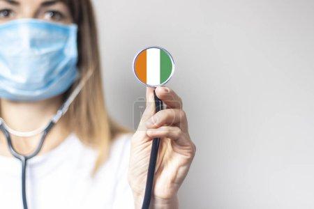 Photo pour Femme médecin dans un masque médical tient un stéthoscope sur un fond clair. Ajouté le drapeau de la Côte d'Ivoire. Concept médecine, niveau de médecine, virus, épidémie . - image libre de droit