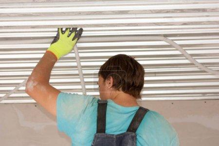 Photo pour Concept de construction. Processus de travail des travailleurs sous le plafond. Orientation horizontale de la feuille - image libre de droit