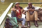 Smiling men with backpacks sitting on pier