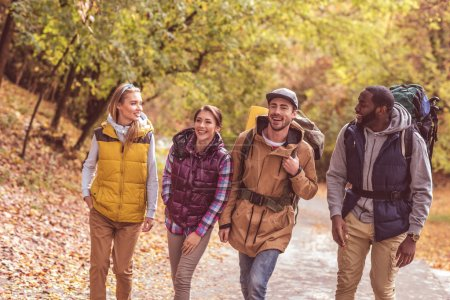 Photo for Group of happy young backpackers walking in autumn forest - Royalty Free Image