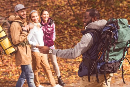 Photo for Young smiling african man pointing with finger and talking with friends in autumn forest - Royalty Free Image