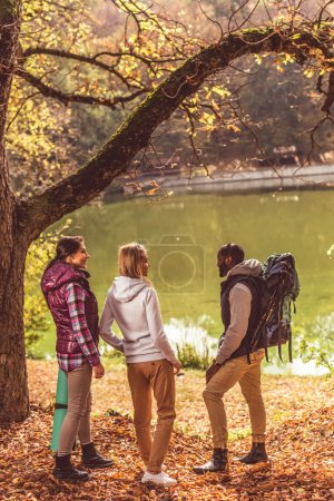 Young backpackers walking near river