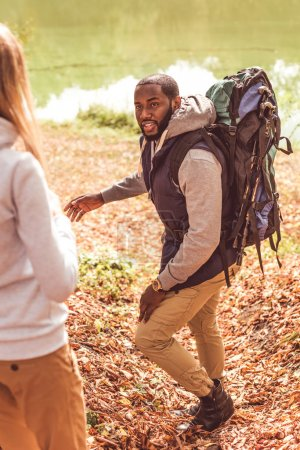Young man with backpack looking at woman