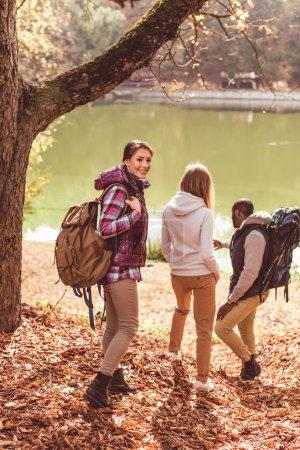 Photo pour Groupe de jeunes randonneurs marchant près de la rivière dans la forêt d'automne - image libre de droit