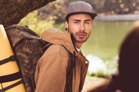 Photo pour Young bearded man traveler with backpack standing under huge tree near river - image libre de droit