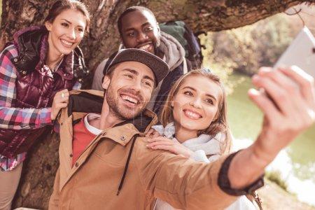 Foto de Grupo de jóvenes de pie cerca de un enorme árbol y tomando selfie cerca de un tranquilo río forestal - Imagen libre de derechos
