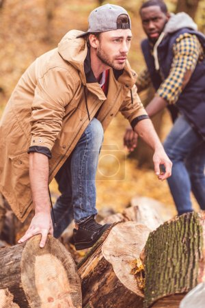Young men near dry stumps in forest